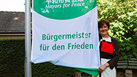 OB Margret Mergen hält die Fahne hoch - Mayors for Peace-Flagge gehisst